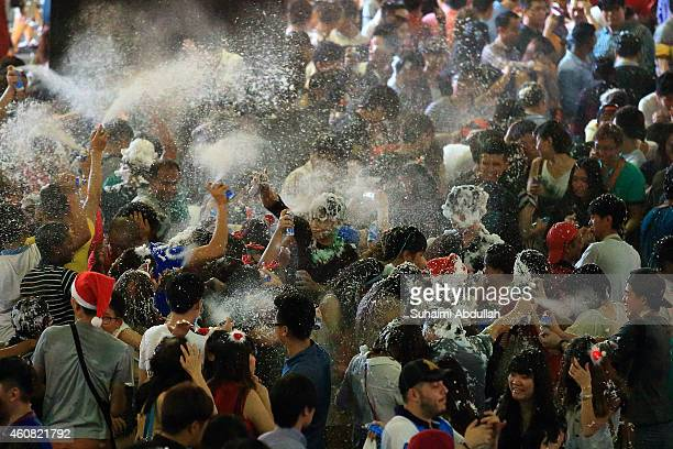 People release snow pray at each other on Christmas eve at Orchard Road on December 24 2014 in Singapore Every year the famous shopping road is...