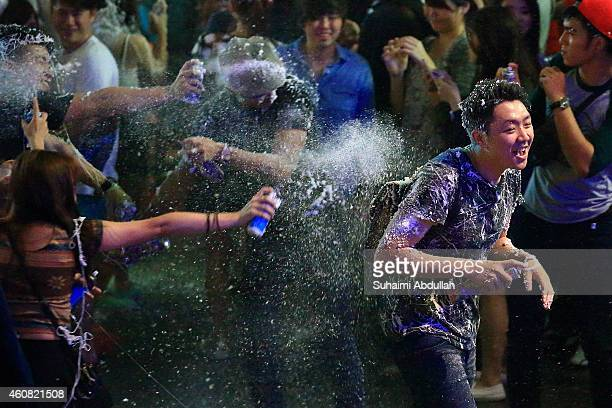 People release snow spray at each other on Christmas eve at Orchard Road on December 24 2014 in Singapore Every year the famous shopping road is...