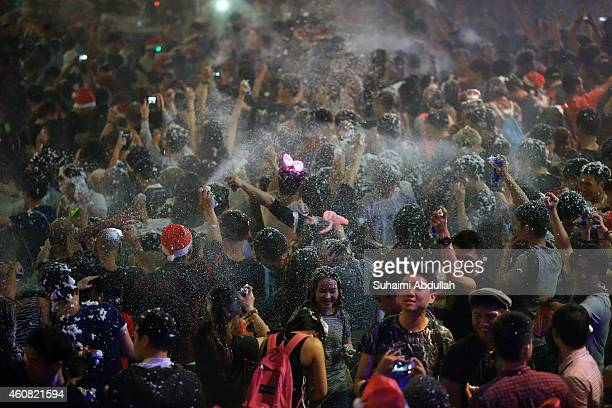 People release snow spray at each other to usher in Christmas along Orchard Road on December 25 2014 in Singapore Every year the famous shopping road...