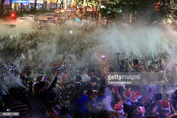 People release snow spray collectively at each other to usher in Christmas along Orchard Road on December 25 2014 in Singapore Every year the famous...