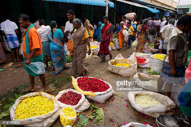 People remain busy in buying and selling flowers in a wholesale market in Madurai