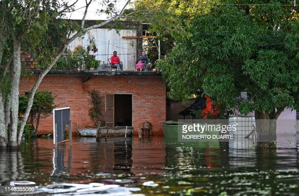 People remain in their flooded house in Puerto Falcon Paraguay on May 25 after heavy rains in the past weeks caused the overflowing of the Paraguay...