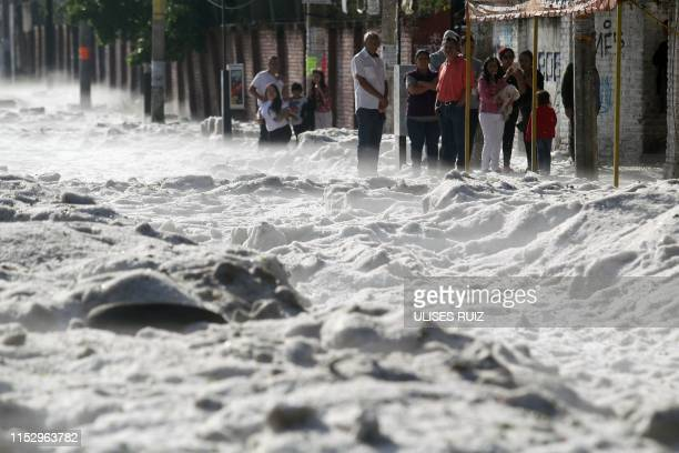 People remain on the sidewalk of a street covered with hail in the eastern area of Guadalajara, Jalisco state, Mexico, on June 30, 2019. - The...