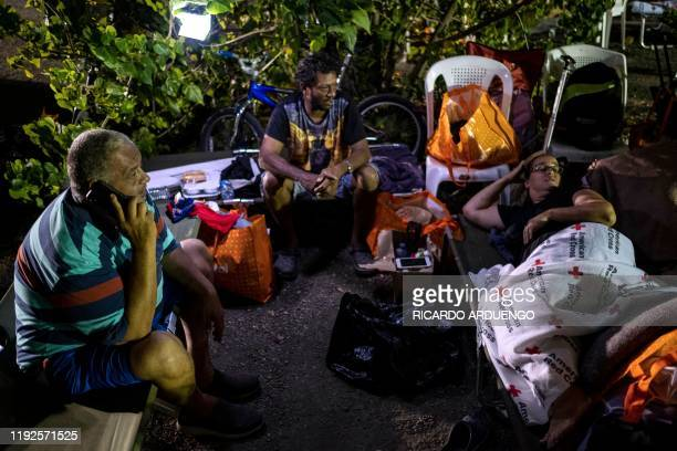 TOPSHOT People remain outdoors under tents and using portable lights for fear of possible aftershocks after an earthquake hit the island in Guanica...