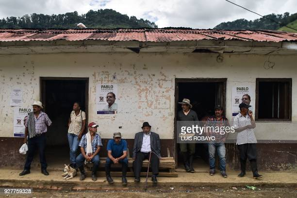 People remain outside a house displaying political propaganda of Pablo Catatumbo senate candidate for the Common Alternative Revolutionary Force...