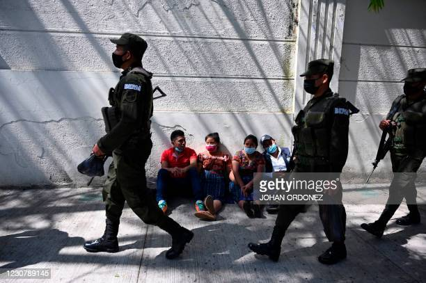 People remain outside the Ministry of Foreign Affairs in Guatemala City on January 25 after giving details of their relatives who might be in the...