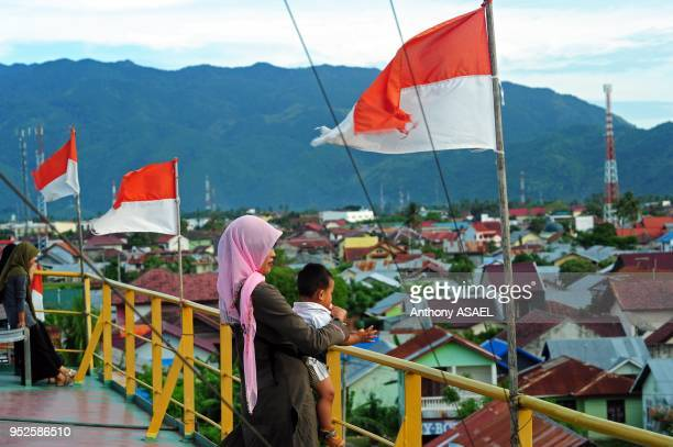 people remembering the Tsunami at top of ship found 5km inland with indonesian flag Banda Aceh Sumatra Indonesia
