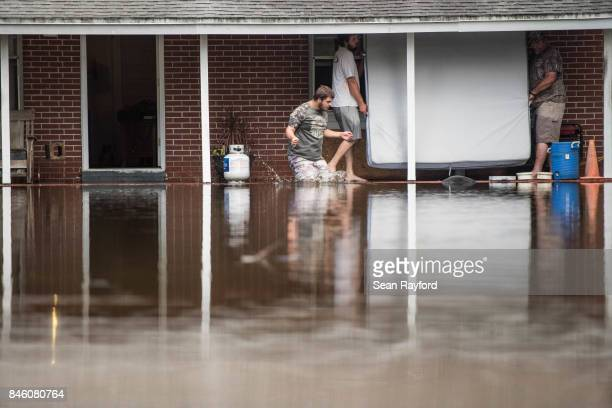 People remove a mattress from a home inundated by flood waters caused by Hurricane Irma September 12 2017 near Palatka Florida Millions of people and...