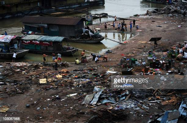 People remove belongings as parking lot and freight yard submerged by floods are being demolished near water area where the Yangtze River and...