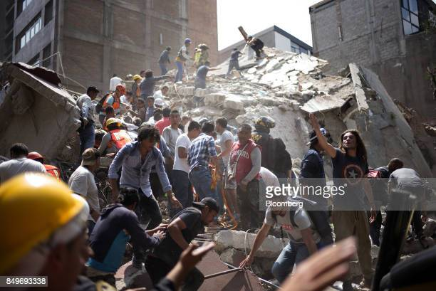 People remove debris from a collapsed building following an earthquake in the neighborhood of Condesa Mexico City Mexico on Tuesday Sept 19 2017 A...