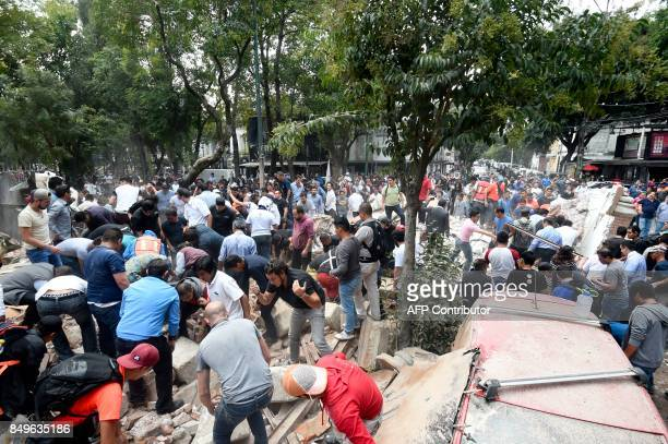 People remove debris of a building which collapsed after a quake rattled Mexico City on September 19 2017 A powerful earthquake shook Mexico City on...