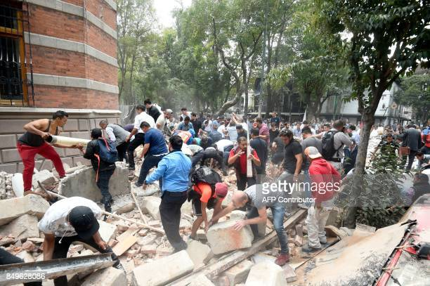 TOPSHOT People remove debris of a damaged building after a real quake rattled Mexico City on September 19 2017 moments after an earthquake drill was...