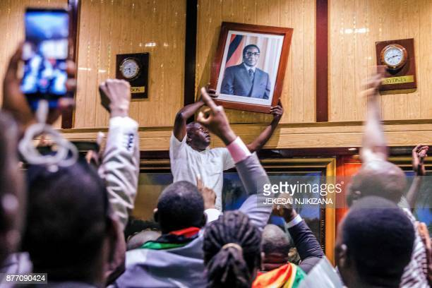 People remove from the wall at the International Conference centre where parliament had their sitting the portrait of former Zimbabwean President...