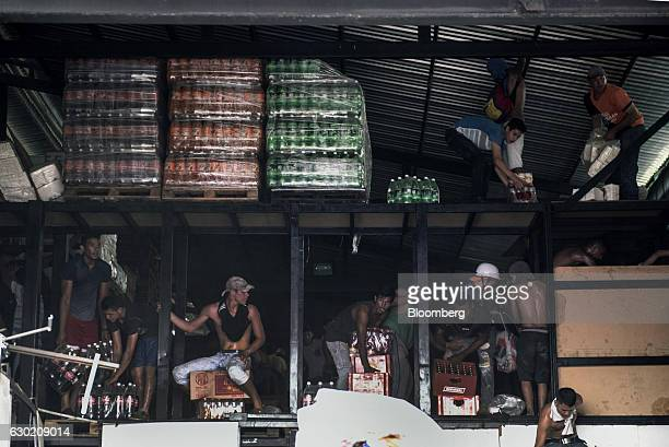 People remove goods from a food warehouse as looting takes place during a protest in La Fria Tachira Venezuela on Saturday Dec 17 2016 The largest...