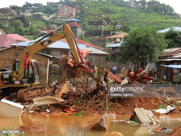 People remove the wreckage at Regent region of Freetown after landslide struck the capital of the west African state of Sierra Leone on August 15...