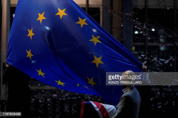 People replace the United Kingdom's flag with a European Union's flag outside the European Union Parliament in Brusselson Brexit Day January 31 2020...