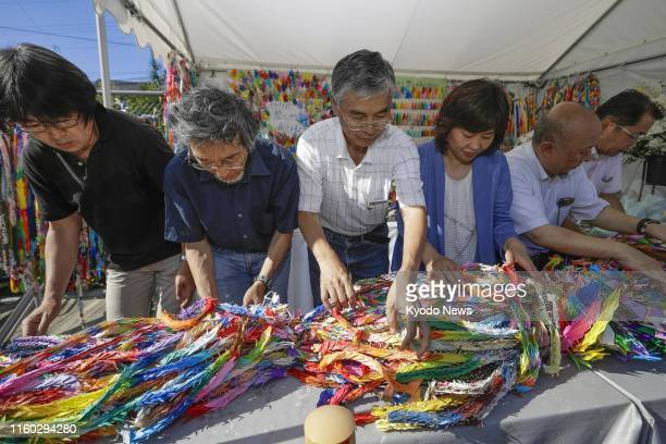 People representing a nonprofit organization engaging in community-enhancement activities in Uji, Kyoto Prefecture, pray on Aug. 8 at an altar set up...