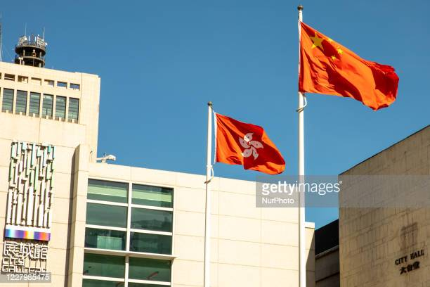 People Republic of China and the Hong Kong SAR flag fly outside of City Hall and the City Gallery in Hong Kong, China, on August 8, 2020.