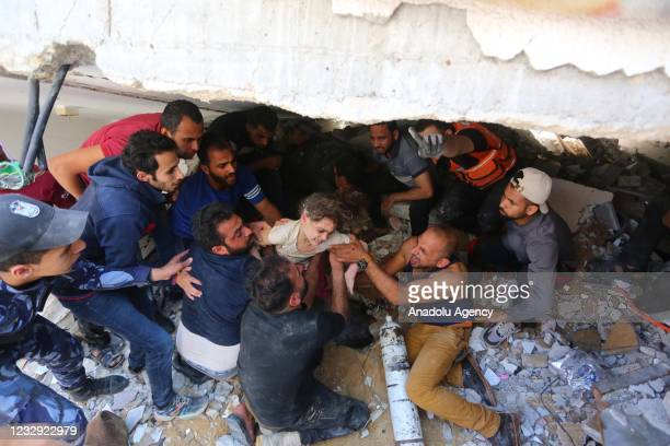 People rescue a wounded child from a debris as search and rescue works continue at a debris of a building after airstrikes by Israeli army hit...