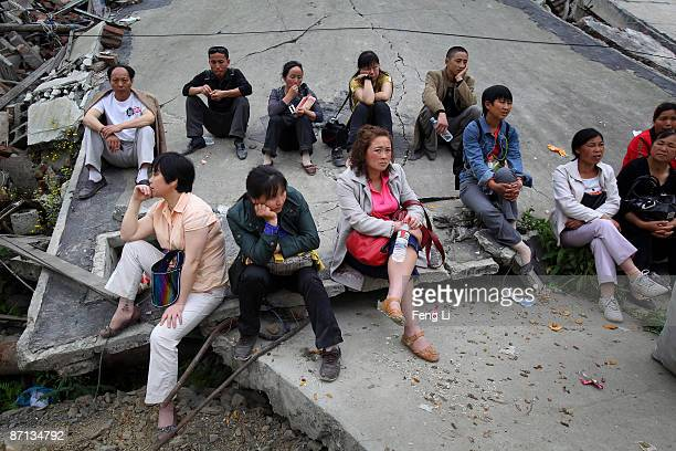 People rest after a ceremony to mourn Sichuan earthquake victims at the ruins of earthquakehit Beichuan county during the one year anniversary of the...