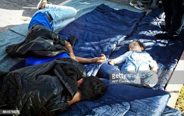People rest as Afghan refugees occupy the main square of the town of Mytilene on October 22 2017 on the island of Lesvos demanding their transfer to...