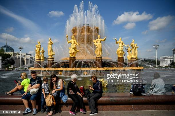 People rest by the famous Druzhba Narodov fountain in the AllRussia Exhibition Centre a trade show and amusement park with temperatures at around 25...