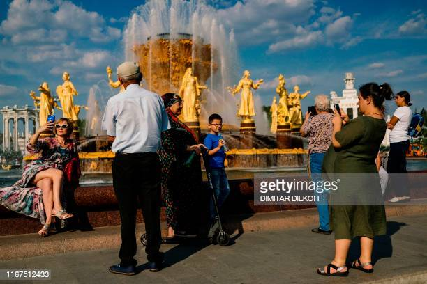 People rest by the famous Druzhba Narodov fountain in the AllRussia Exhibition Centre a trade show and amusement park in Moscow on September 12 2019
