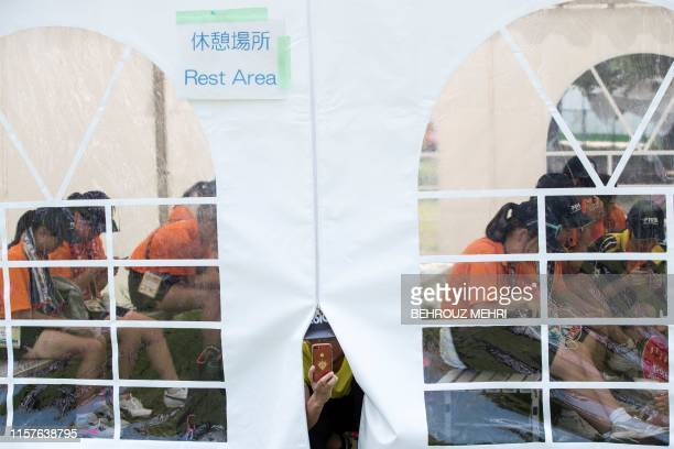 People rest inside a cooling tent installed at Shiokaze Park during the beach volleyball test event for the Tokyo 2020 Olympic Games in Tokyo on July...