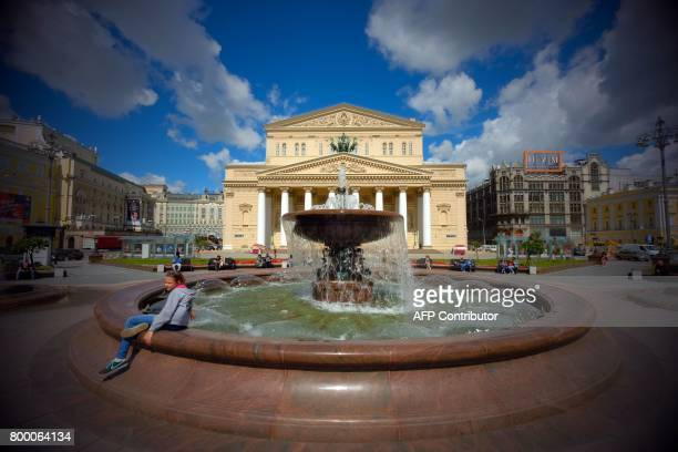 People rest near a fountain in front of the Bolshoi Theatre in central Moscow on June 23 2017 / AFP PHOTO / Yuri KADOBNOV