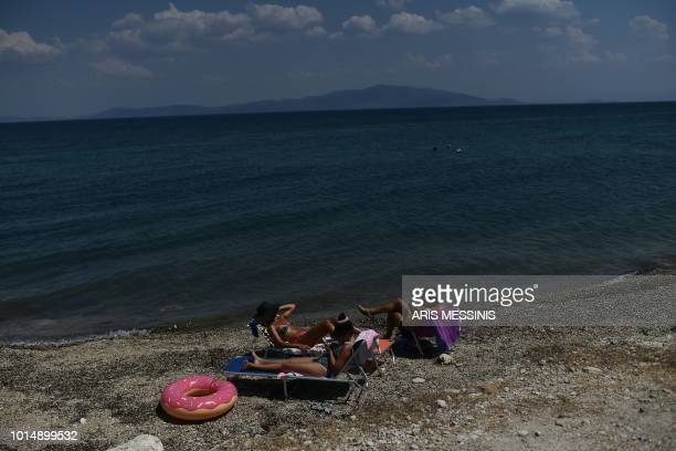 People rest on a beach in the town of Mytilene on the Greek island of Lesbos on August 3 2018