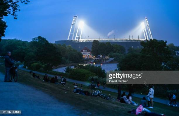 People rest on the dike near the Wohninvest Weserstadion where SV Werder Bremen and Bayer 04 Leverkusen perform their Bundesliga match behind closed...