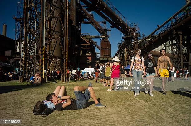 People rest on the ground of Vitkovice ironworks area during the Colours of Ostrava music festival on July 21 2013 in Ostrava city North Moravia AFP...