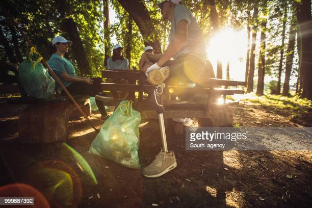 people resting after cleaning public park - disability collection stock pictures, royalty-free photos & images