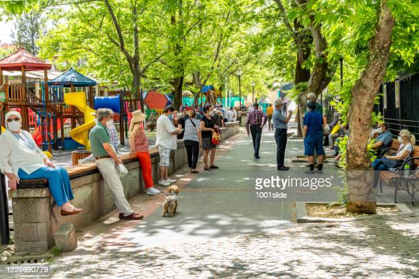 people resting at park which name is swan park (kugulu park) with coronavirus mask - ankara turkey stock pictures, royalty-free photos & images