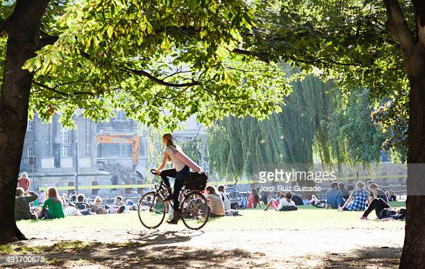 People resting in a park on the banks of the river Spree in Berlin.