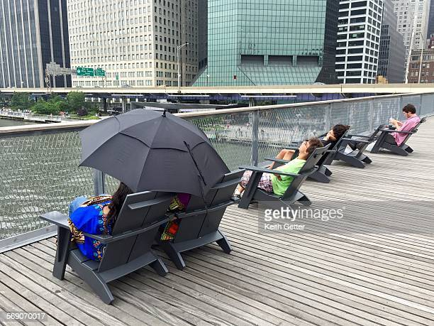 People resting on lounge chairs on the upper deck of an urban park set on a pier on top of the East River in lower Manhattan NYC on a summer...