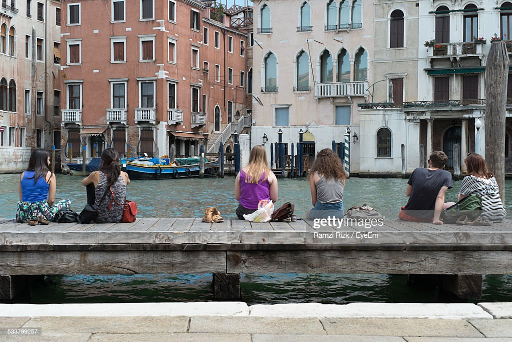 People Resting On Wood Pier Over Canal : Foto stock
