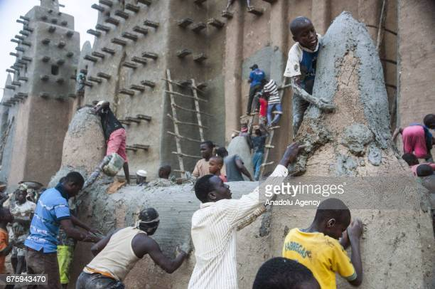 People restore Great Mosque of Djenne with Mud in Mali on April 30, 2017. The Great Mosque of Djenne listed in UNESCO as a World Heritage Site is the...