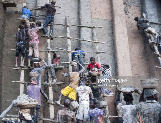 People restore Great Mosque of Djenne with Mud in Mali on April 30 2017 The Great Mosque of Djenne listed in UNESCO as a World Heritage Site is the...