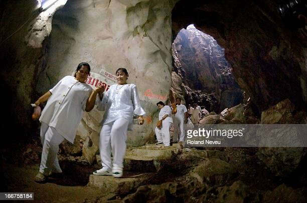 People return from a shrine in a far corner of the Wat Tham Bo Ya cave. During Khao Phansa , anyone in Thailand can go to meditate in a pagoda or...