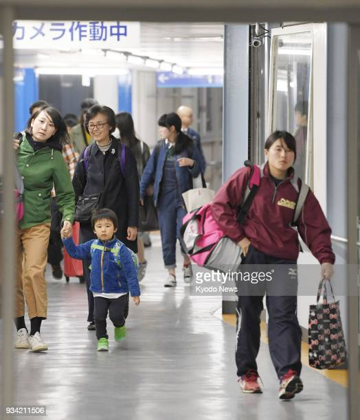 People return to a port in Osaka Prefecture on March 19 after a ferry carrying more than 500 passengers hit a steel buoy the previous day off Akashi...