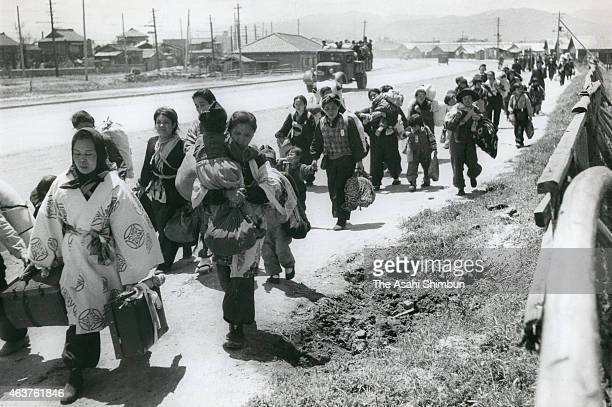 People returning from Japanruled Korea and China walk on the street circa November 1945 in Fukuoka Japan