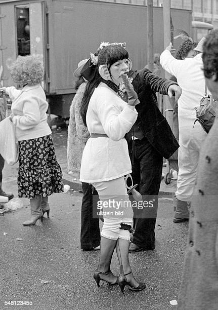 people Rhenish carnival Rose Monday parade 1981 woman with a mask and in a carnival costume watches the parade aged 30 to 40 years DDuesseldorf Rhine...