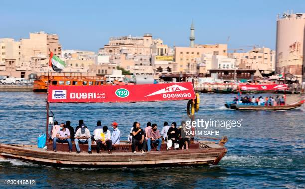 People ride a boat at the Ras El-Khor wildlife sanctuary near the old quarter of the Gulf city of Dubai, on January 6, 2021.