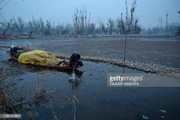 People ride a boat during a cold morning at the interiors of Dal Lake, in Srinagar on December 21, 2020.