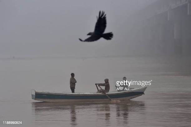 TOPSHOT People ride a boat on the Ravi River during a cold and foggy morning in Lahore on December 16 2019