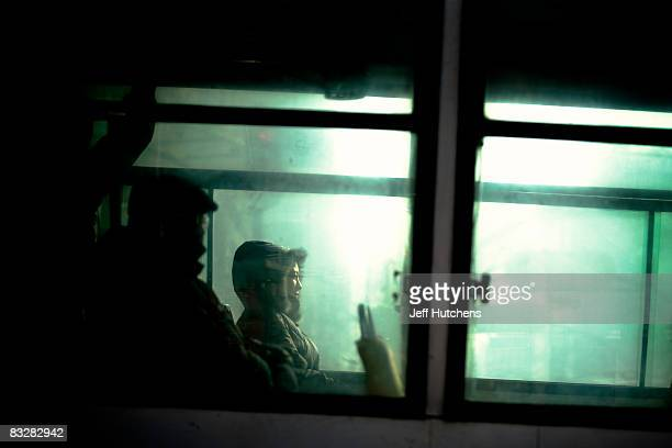 People ride a bus through frigid streets during the cold of northern China's winter while heavy industry factory smoke filters up to the gray sky on...
