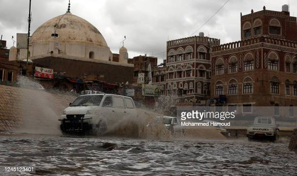 People ride a car in flooded waters near historical buildings of the old quarter of Sana'a on June 04, 2020 in Sana'a, Yemen.