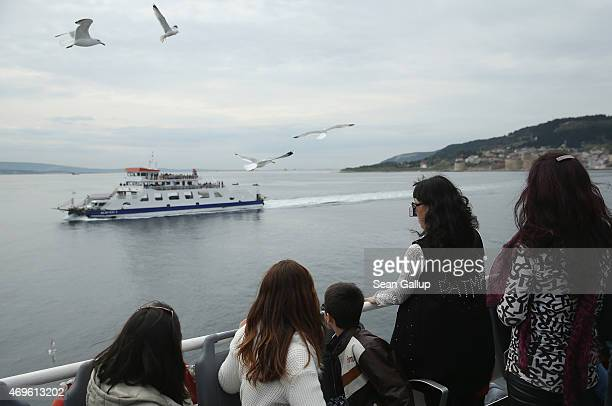 People ride a ferry across the Dardanelles strait to the Gallipoli peninsula in the same area where 100 years before British and French warships...