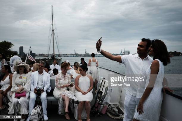 People ride a ferry to enjoy dinner at the annual 'Diner en Blanc' September 17 2018 on Governors Island in New York City Diner en Blanc began in...